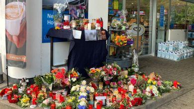 Blumen und Kerzen sind vor der Tankstelle, in der der Mord passierte