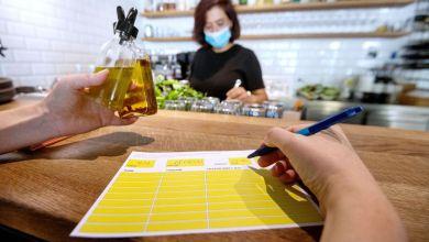 Eine Angestellte in einer Pizzeria hat einen Mundschutz an, während eine Kollegin auf der Theke einen Zettel zur Besucherregistrierung vorausfüllt