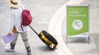 Urlauberin am Flughafen - Schild «Corona-Testzentrum»