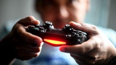 Mann spielt mit der Spielekonsole Playstation