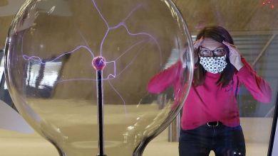 Frau schaut durchs phaeno-Schaufenster auf ein Experiment-Rätsel