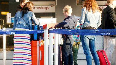 Urlauber stehen an einem Check-In-Schalter am Düsseldorfer Flughafen an.