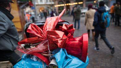 Eine rote Glocke und eine Schleife, die einen Stand auf dem Weihnachtsmarkt dekoriert hatten, liegen beim Abbau des Marktes im Müll