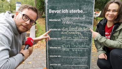Holger Tapper und Nadine Rathke hocken vor einer Tafel-Stele im Nordpark Magdeburg