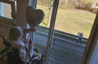 Renate und Georg Tahler feiern ihren Hochzeitstag am Fenster eines Seniorenheims.