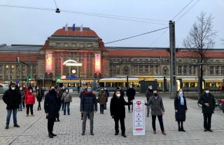 Händler vorm rot erleuchteten Leipziger Bahnhof