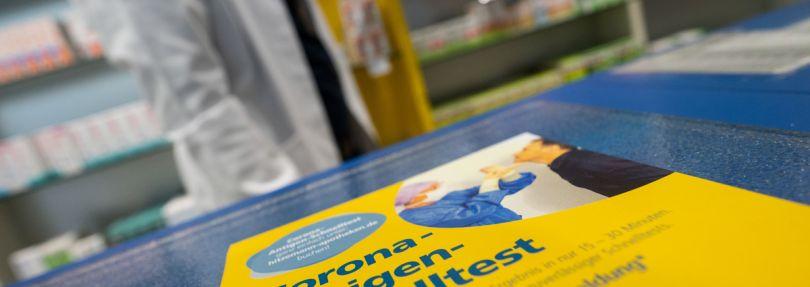 Flyer, der auf einen Corona-Antigen-Schnelltest hinweist, liegt in einer Apotheke auf dem Tresen