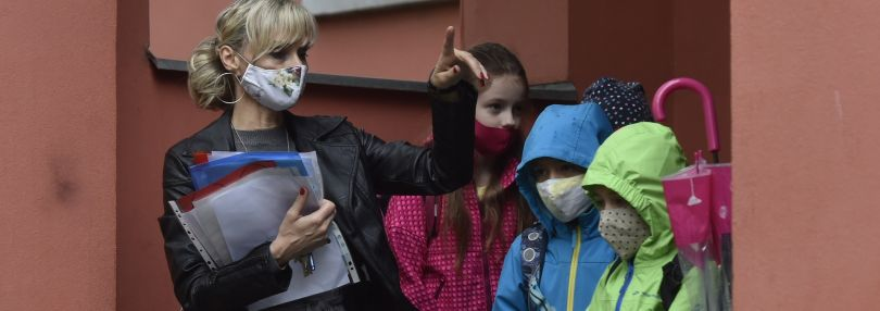 Tschechien, Ostrava: Eine Frau mit Mundschutz steht neben Grundschülerinnen und Grundschülern an der Matiční-Grundschule.