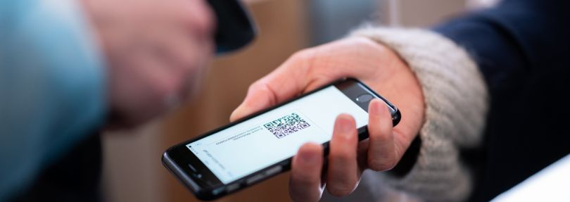 Frau lässt am Eingang eines Corona-Schnelltest-Zentrums einen QR-Code auf ihrem Smartphone abscannen.