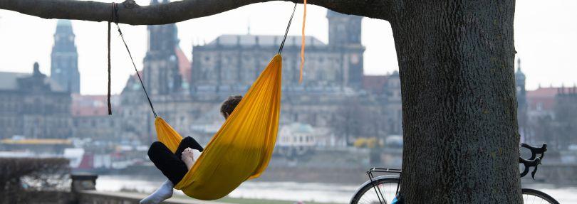 Ein Mann liegt am Ufer der Elbe vor der Kulisse der Altstadt in einer Hängematte.