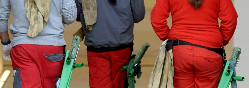 Gebäudereiniger gehen mit ihren Reinigungswerkzeugen am Gürtel in ein Gebäude.
