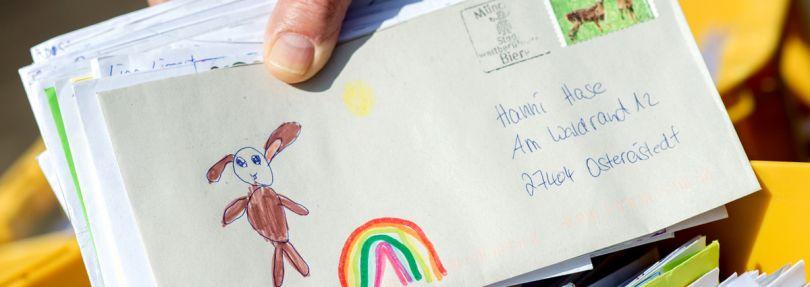Ein Mitarbeiter des Osterpostamts hält vor dem Gemeindehaus von Ostereistadt einen Brief in den Händen, der einen gemalten Regenbogen und die Aufschrift «Wir bleiben Zuhause!» zeigt.
