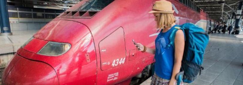 Junge Frau mit Handy vor einem Zug