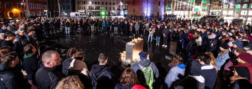 Trauernde stehen auf dem Marktplatz in Halle
