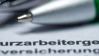 ILLUSTRATION - Zwei Kugelschreiber liegen auf einem Antragsformular für Kurzarbeitergeld.
