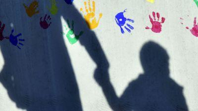 Ein Mann mit einem Kind auf dem Arm und einem an der Hand wirft einen Schatten auf eine mit bunten Handabdrücken bemalte Wand einer Kindertagesstätte