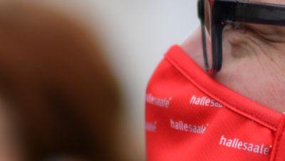 Carolin Loh und Thomas Salwiczek 8R9 vom Stadtmarketing Halle tragen wiederverwendbare Mund-Nasen-Behelfsmasken mit der Stadtmarke von Halle/Saale auf dem Marktplatz der Stadt. Die roten Masken werden unter anderem in der Tourist-Information angeboten und