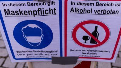 Ein Schild weist auf die Maskenpflicht und das Alkoholverbot hin