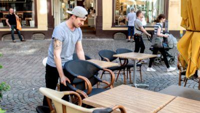 Mitarbeiter eines Cafés stellt Stühle und Tische für Gäste bereit