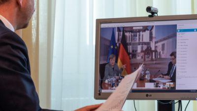 Michael Kretschmer (CDU), Ministerpräsident von Sachsen, sitzt in einem Büro in der Staatskanzlei vor einem Computerbildschirm und spricht während einer Schaltkonferenz per Video mit Bundeskanzlerin Angela Merkel (CDU, l.) und Markus Söder (CSU), Minister