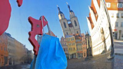 An einer Skultur auf dem Wittenberger Marktplatz hängt ein Mund- Nasen- Schutz.