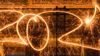 Die Zahl 2021 ist mit einer Wunderkerze während einer Langzeitbelichtung vor dem Brandenburger Tor in den Abendhimmel geschrieben.
