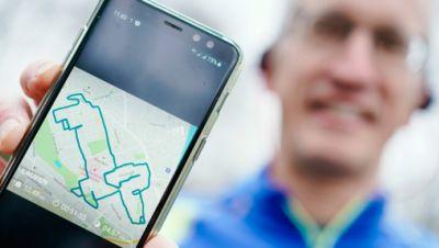 Norbert Asprion hält sein Mobiltelefon mit dem Bild einer von ihm gelaufenen Wegstrecke in Form eines Hundes in den Händen.