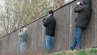 Schaulustige fotografieren neben einer Lärmschutzwand mit ihren Smartphones eine Unfallstelle