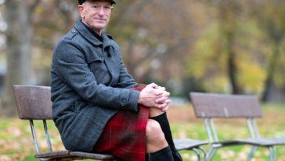 Mark Bryan, Influencer im Socialen Netzwerk Instagram, sitzt auf einer Bank.
