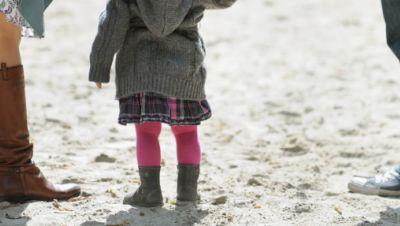 Kind steht auf einem Spielplatz zwischen seinen Eltern