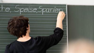 Lehrerin schreibt in einer Grundschule Worte an eine Tafel.