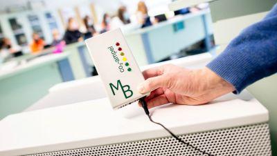 Ein Lehrer hält eine gelb leuchtende CO2-Ampel vor einem Luftfiltergerät in der Hand.
