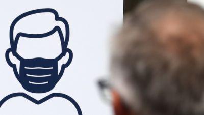 """Aushang an einer Bankfiliale in der Innenstadt steht in mehreren Sprachen """"Maskenpflicht Bitte tragen Sie einen Mund-Nasen-Schutz"""", ein Mann geht daran vorbei."""