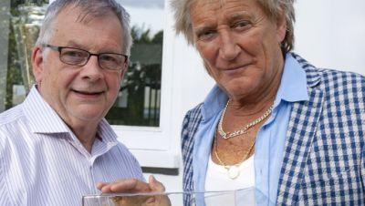 Rod Stewart steht neben dem Chefredakteur Fachzeitschrift «Railway Modeller», der ihm einen Modelleisenbahn-Waggon, überreicht.