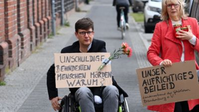 """Eine Frau und ein Mann im Rollstuhl gehen mit Plakaten """"Unschuldige behinderte Menschen töten. Warum?"""" und """"Unser aufrichtiges Beileid"""" zum Eingang der Einrichtung des diakonischen Anbieters Oberlinhaus."""