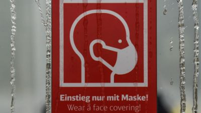 """Fensterscheibe mit Schild """"Einstieg nur mit Maske!"""" und gefrorenen Wassertropfen"""