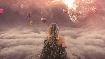 Frau sitzt im Himmel schwebend, Heißluftballons um sie herum, die Erde in der Ferne